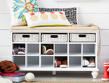 An entryway organizer filled with sneakers, topped with a seating bench and deocrative pillows.