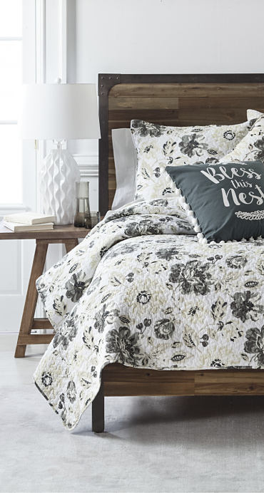 A bed made with a gray and white floral comforter.