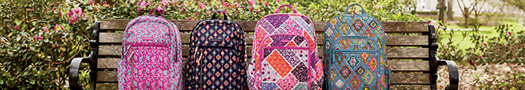 4 different multi-color patterned Vera Bradley backpacks on a wooden park bench.
