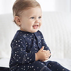 A baby boy wearing a navy onesie with white dots. Shop baby boys