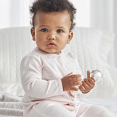 A baby girl wearing a white onesie. Shop baby girls