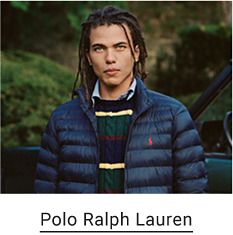 A man wears a green, blue, red and yellow corded sweater, with a blue puffy Ralph Lauren jacket on top of it. Polo Ralph Lauren.