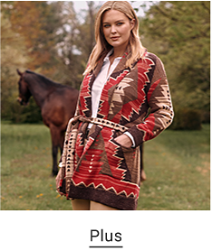 A woman in a white button up shirt with a red and brown Aztec jacket over top. Plus.