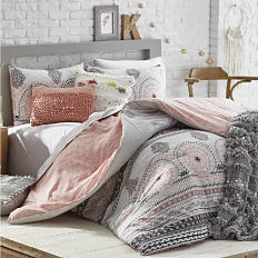 A bed with a printed comforter, a throw blanket and a variety of decorations. Shop dorm shop.