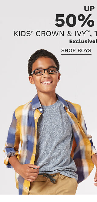 A boy wearing a gold, blue & white plaid long sleeved button front shirt over a gray T shirt & beige pants standing next to a girl wearing a pink, brown & white plaid sleeveless top & distressed blue jeans. Up to 50% off kids' Crown & Ivy, True Craft & more. Exclusively at Belk. Shop boys.