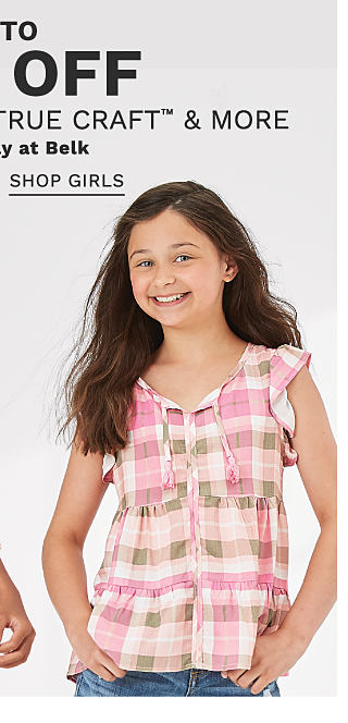 A boy wearing a gold, blue & white plaid long sleeved button front shirt over a gray T shirt & beige pants standing next to a girl wearing a pink, brown & white plaid sleeveless top & distressed blue jeans. Up to 50% off kids' Crown & Ivy, True Craft & more. Exclusively at Belk. Shop girls.