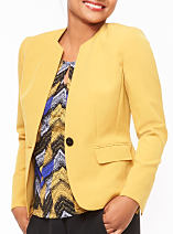 A woman wearing a yellow blazer and black skirt with a multi-colored print blouse. Shop suits.