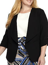 A woman wearing a black blazer over a white top with a multi-colored print skirt. Shop suits.