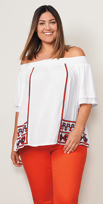 A woman wearing a white and red cold-shoulder top and red pants. Shop tops.
