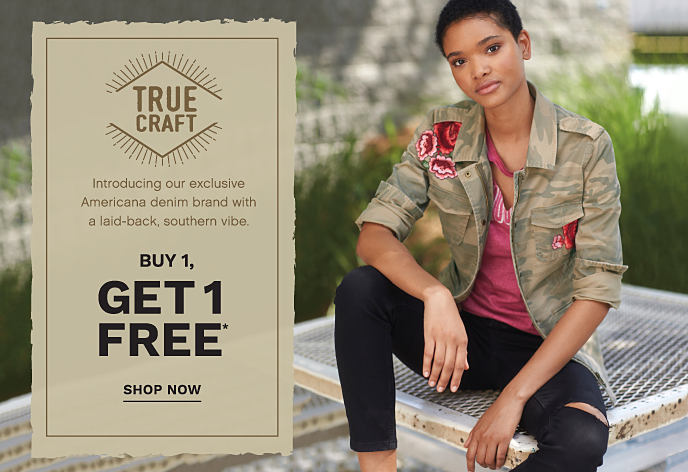 A young woman wearing a camo jacket over a distressed burgundy tee and distressed black denims from True Craft. Introducing True Craft, our exclusive Americana denim brand with a laid-back, southern vibe. Buy 1, Get Free True Craft. Shop now.