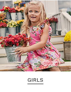 A little girl wearing a pink, white and green floral sleeveless dress. Shop girls.