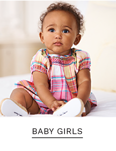 A baby girl wearing a pink, white, yellow and blue plaid dress. Shop baby girls.