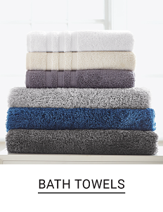 A stack of folded bath towels in a variety of colors. Shop bath towels.