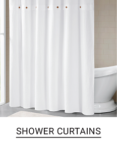 A white shower curtain in front of a white bathtub. Shop shower curtains.