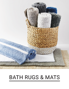 A wicker basket full of rolled up bath rugs & mats in a variety of colors & styles. Shop bath rugs & mats.