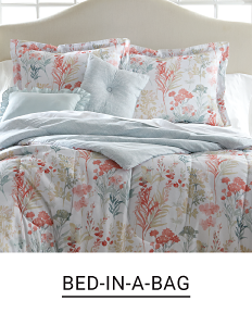 A bed made with a multi colored floral print quilt & matching pillows. Shop bed in a bag.