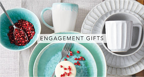 An assortment of silverware & teal & white plates, bowls & mugs. Engagement Gifts. Shop now