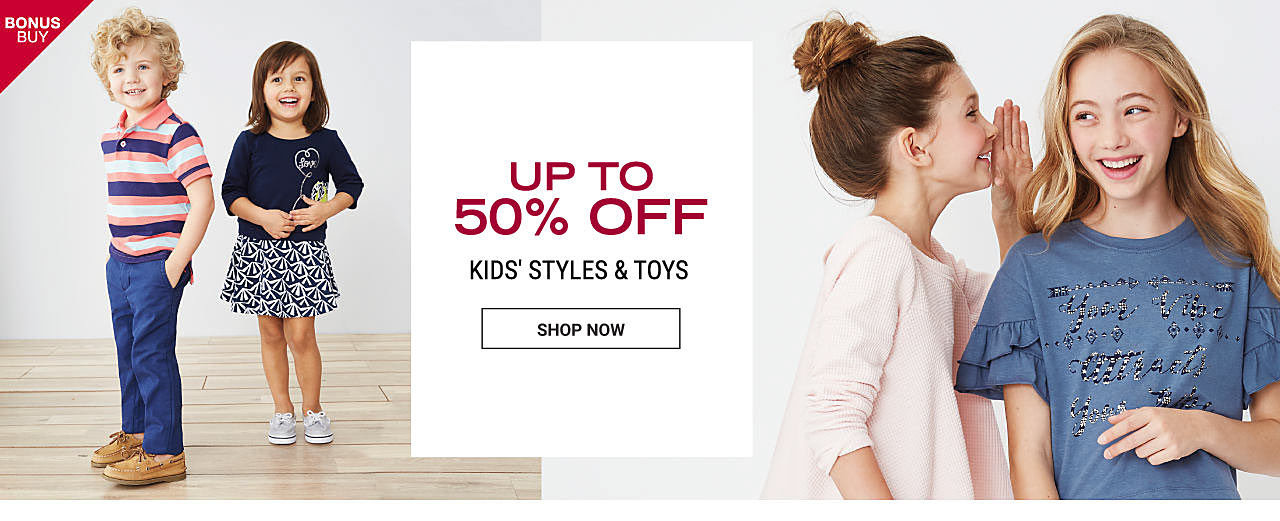 A boy wearing a coral, teal & navy horizontal striped polo, blue pants & beige deck shoes. A girl wearing a navy top, a navy & white patterned skirt & light blue sneakers. Up to 50% off kids sportswear from Crown & Ivy, True Craft, Carter's & more. Shop now.