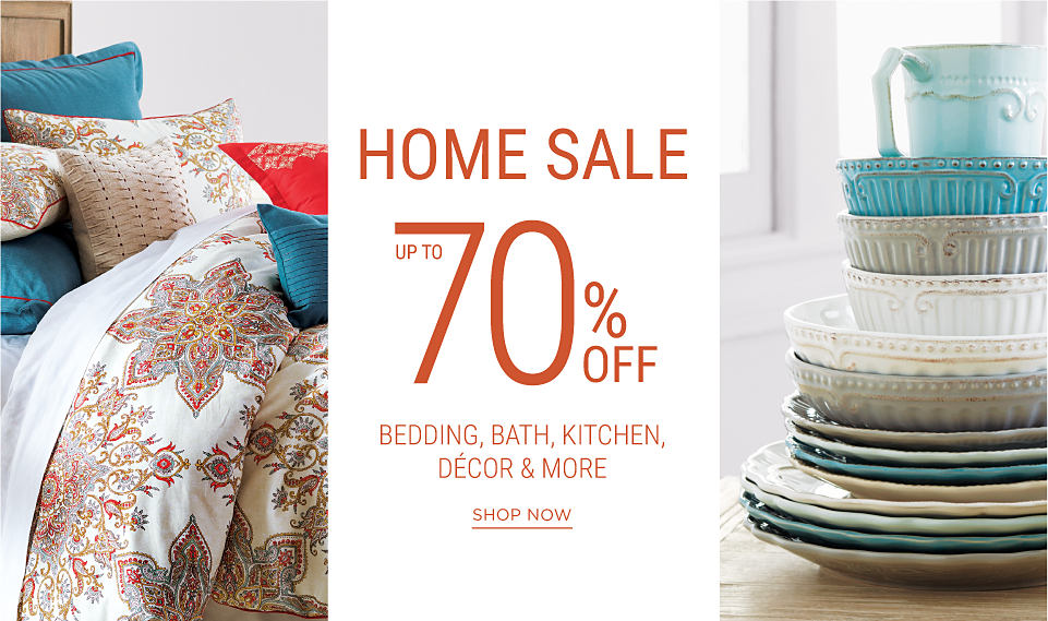 A bed made with a multi-colored print comforter and several pillows in a variety of colors. An ornate ceramic mug resting in a stack of ceramic bowls in a variety of colors, stacked on a stack of ceramic plates in a variety of colors. Home Sale. Up to 70% off bedding, bath, kitchen, decor & more. Shop now.