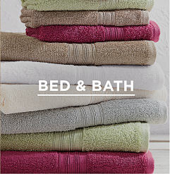 A stack of green, burgundy, gray & white folded bath towels. Shop bed & bath.
