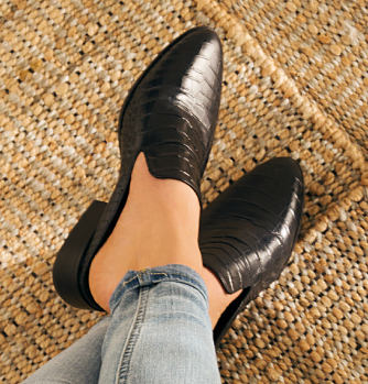 A woman wearing a pair of black leather mules. Mules. Shop Now.