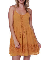 A woman wearing a burnt yellow colored sun dress. Shop dresses.