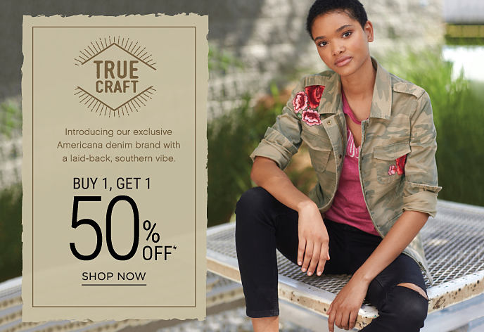 A young woman wearing a camo jacket over a distressed burgundy tee and distressed black denim from True Craft. Introducing True Craft, our exclusive Americana denim brand with a laid-back, southern vibe. Buy 1, Get 1 50% off. Discounted item must be of equal or lesser value. Shop now.