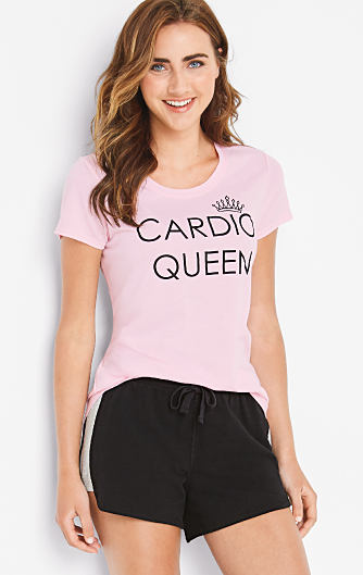 "A young woman wearing a pink ""Cardio Queen"" graphic tee and black shorts. Shop activewear."