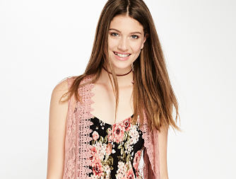 A woman wearing a floral top with a lace vest layered over it, Fast Fashion Under $25. Shop now.