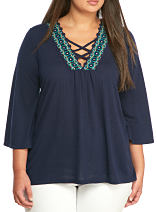 A woman wearing a navy empire waist top with teal detail along the neckline. Shop tops.