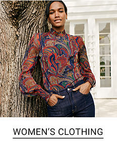 A woman in a paisley print top and jeans. Shop women's clothing.