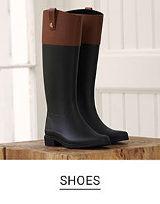 A pair of black and brown tall boots. Shop shoes.