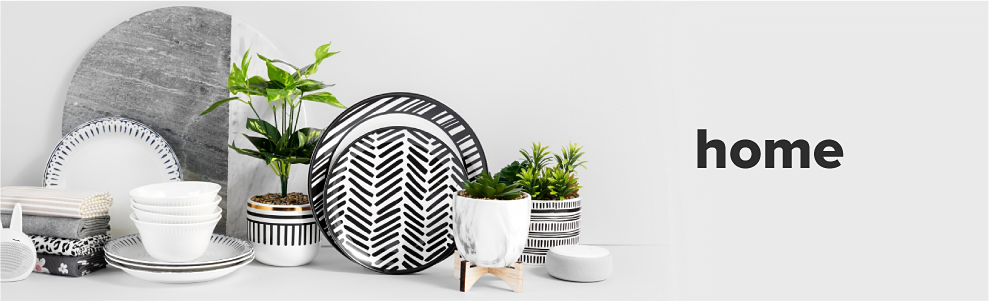 Black and white dinnerware with small plants around it, a white wireless speaker and a black headphone.