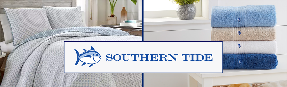 A bedding set in white with greenish blue dots over it. A stack of folded towels in blue, brown, white and navy, each with the Southern Tide fish logo on them. Southern Tide.