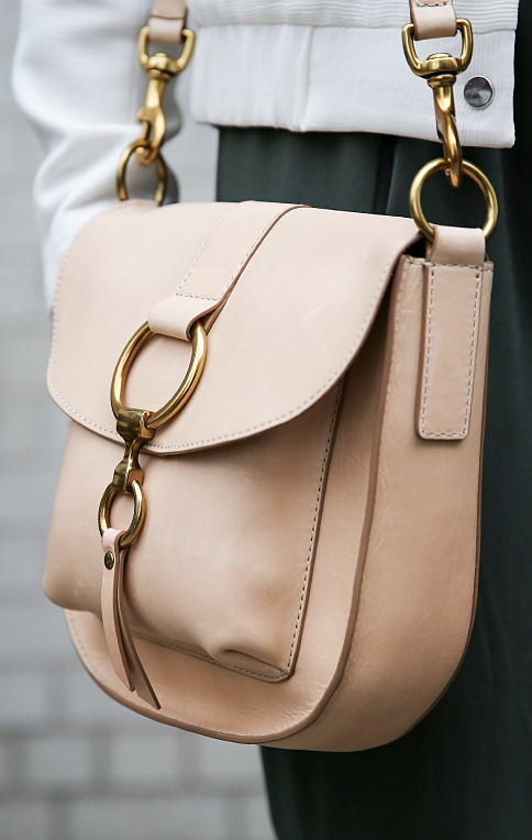 A woman carrying a beige leather handbag with gold hardware detail. Shop designer handbags.
