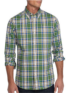 A man wearing a green, blue, black and white plaid button front shirt and black jeans. Shop casual shirts.