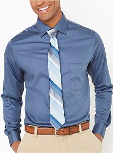 A man wearing a blue button-front dress shirt, a blue striped tie & khaki pants. Shop dress shirts.