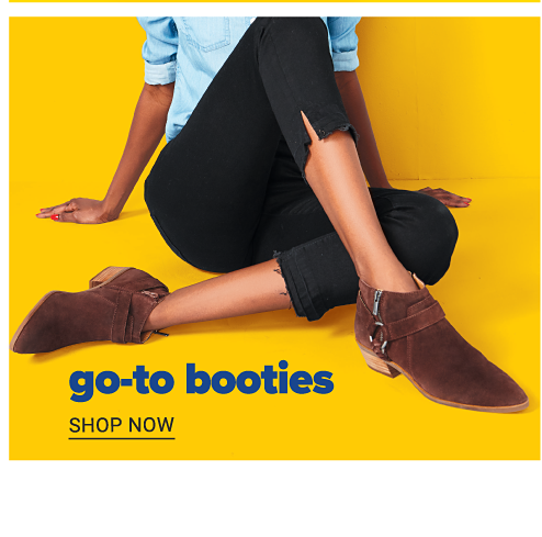 A woman wearing a light blue long sleeved top, black capris & brown suede booties. Go To Booties. Shop now.