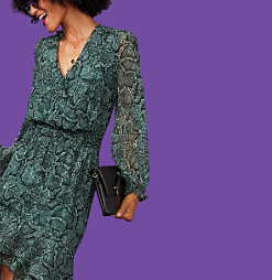 A woman in a green and black snake print dress with long sheer sleeves.