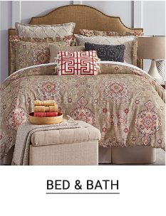 A bed made with a mutl colored patterned print comforter & matching pillows. Shop bed & bath.