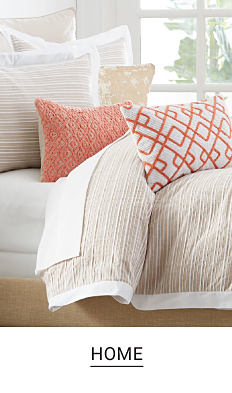 A bed with white and beige bedding and white and coral decorative pillows. Shop home.