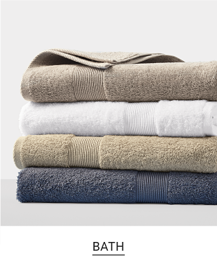 A stack of brightly colored towels in a variety of colors and designs Bath. Shop Now.