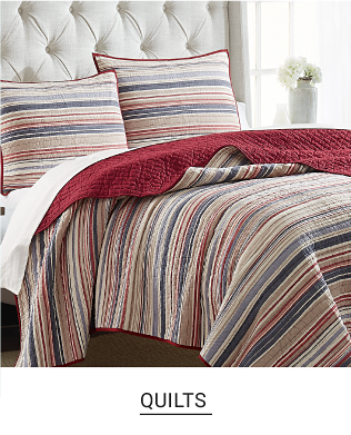 A bed made up with a frey quilt and matching pillows. Quilts. Shop Now.