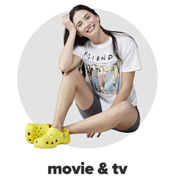 A young woman wearing a white tee with a Friends tv show graphic, bike shorts and yellow slip on shoes. Movie and tv.