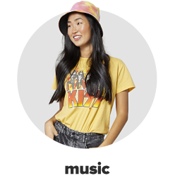 A young woman wearing a yellow tee with a Kiss band graphic, a bucket hat and jeans. Music.