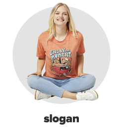 A young woman wearing an orange graphic tee, skinny ankle jeans and white sneakers. Slogan.