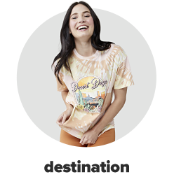 A young woman wearing a white and orange desert graphic tee and orange leggings. Destination.