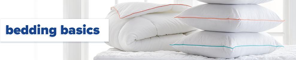 A folded white mattress pad & a stack of white pillows. Bedding basics.