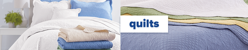 A bed made with a white quilt & white & light blue pillows with a stack of folded quilts on the edge of the bed in a variety of colors. An assortment of quilts in a variety of colors. Quilts.