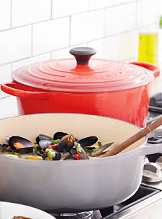A covered red ceramic pot on a white stove next to a gray ceramic pot filled with seafood & vegetables. Shop kitchen.